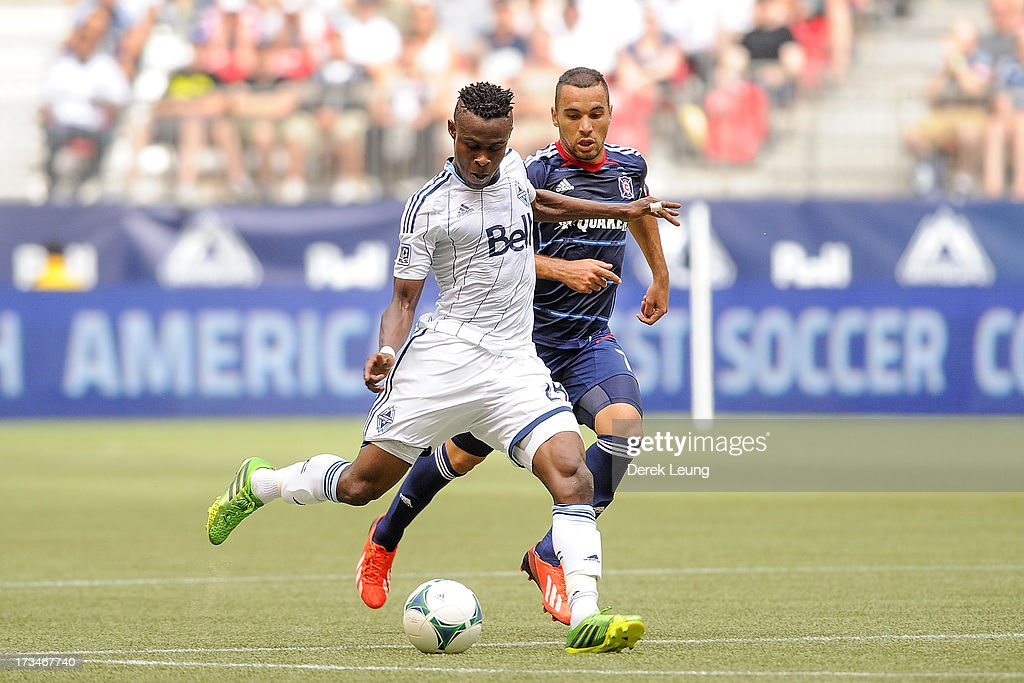 Gershon Koffie #28 of the Vancouver Whitecaps runs with the ball past Alex #71 of Chicago Fire during an MLS Match at B.C. Place on July 14, 2013 in Vancouver, British Columbia, Canada. The Vancouver Whitecaps won 3-1.