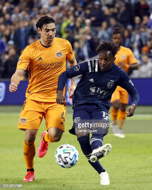 Gerso of Sporting Kansas City shoots as Zarek Valentin of Houston Dynamo defends during the game at Children's Mercy Park on March 07 2020 in Kansas...