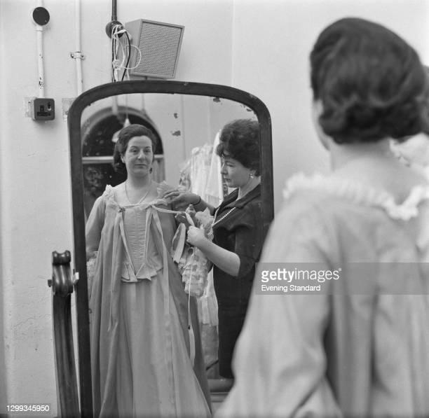 Gertie Stelzel , the wardrobe mistress at the Royal Opera House, dresses Irish soprano Veronica Dunne for a role, UK, November 1966.