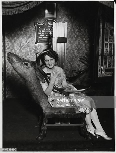 Gertrude Olmstead actress from the 1920's seated on a chair made from the head and body of an elk Undated photograph