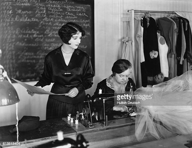 Gertrude Olmstead from the MGM Studios checks the costume design with the dress being made by the costumer