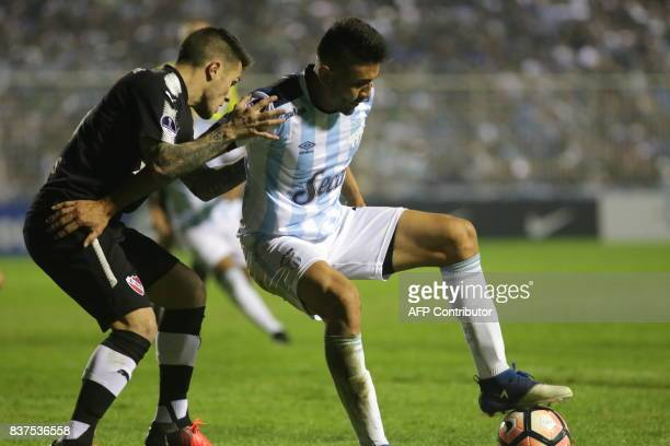 Gervasio Nunez of Atletico Tucuman disputes the ball with Fabricio Bustos of Independiente in their Copa Sudamericana 2017 match in the Jose Fierro...