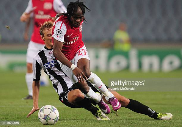 Gervinho of Arsenal battles with Joel Ekstrand of Udinese during the UEFA Champions League play-off second leg match between Udinese Calcio and...