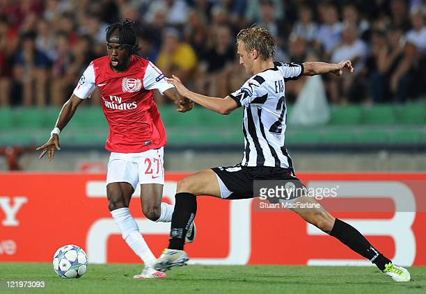 Gervinho of Arsenal breaks past Joel Ekstrand of Udinese during the UEFA Champions League play-off second leg match between Udinese Calcio and...
