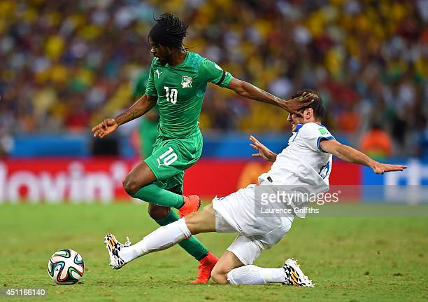 Gervinho of the Ivory Coast is tackled by Vasilis Torosidis of Greece during the 2014 FIFA World Cup Brazil Group C match between Greece and the...