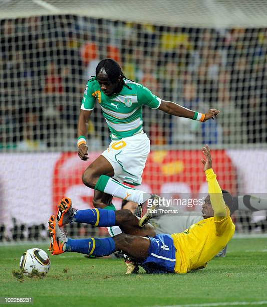 Gervinho of the Ivory Coast leaps over the challenge of Juan of Brazil during the 2010 FIFA World Cup South Africa Group G match between Brazil and...