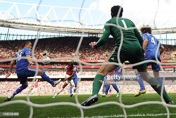 Gervinho scores Arsenal's goal past John Terry and Petr Cech of Chelsea during the Barclays Premier League match between Arsenal and Chelsea at...
