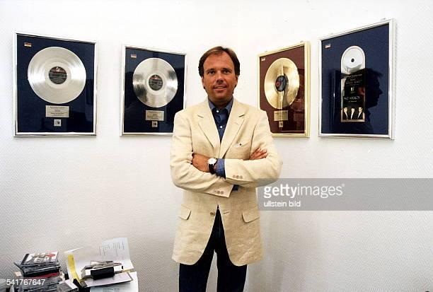 Geschäftsführer der Firma 'Hansa Music'in seinem Büro vor gerahmten goldenenund Platinschallplatten 1997