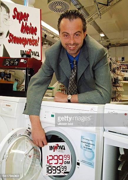 Geschäftsführer von Innova Porträt weist auf ein Preisschildeiner Waschmaschine mit heruntergesetzte Preis hin 1999