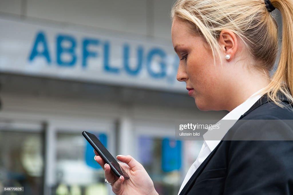 Geschäftsfrau schreibt am Flughafen SMS. Roaming Gebühren im Ausland : News Photo