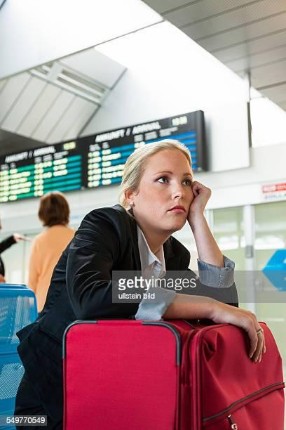 Geschäftsfrau wartet auf ihren Abflug am Flughafen. Symbolfoto für Wartezeiten, Flugausfälle und Streiks