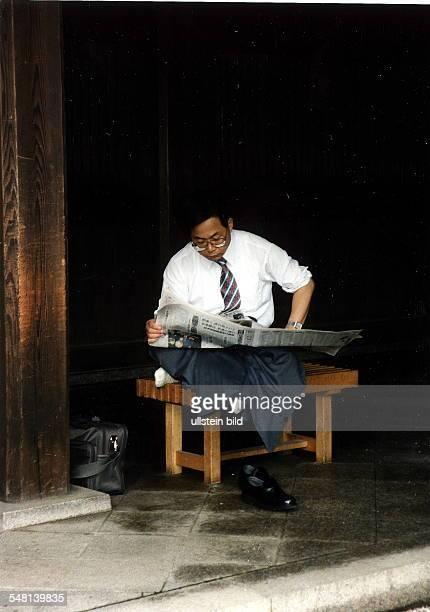 Geschäftsmann in Tokio macht Pause und liest Zeitung