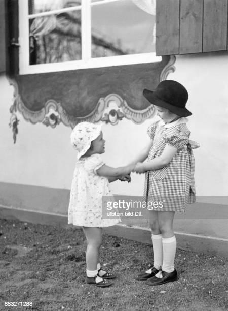 Geschwister zwei kleine Schwester tragen ein Kleid ein weissrot geblümtes Waschkleid und ein weissrot kariertes Kleid mit Schleife