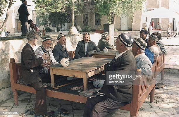 """Geselliges Leben in Usbekistan: Eine Gruppe Senioren trifft sich auf dem Platz """"Labe-Haus"""" in Buchara zum Klönen und Teetrinken. Die Männer haben es..."""