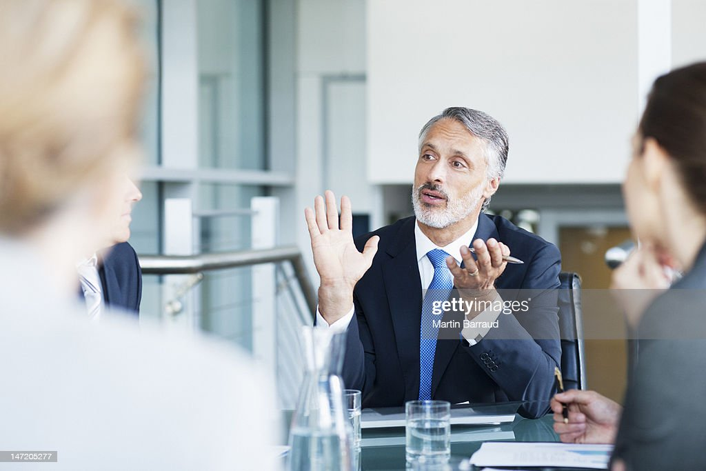 Gesturing businessman leading meeting in conference room : Stock Photo