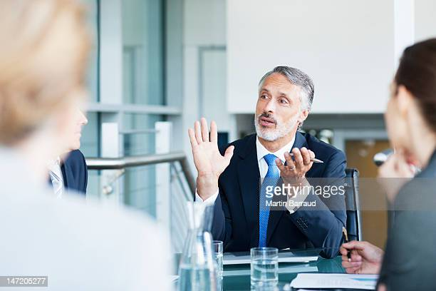gesturing businessman leading meeting in conference room - businessman stock pictures, royalty-free photos & images