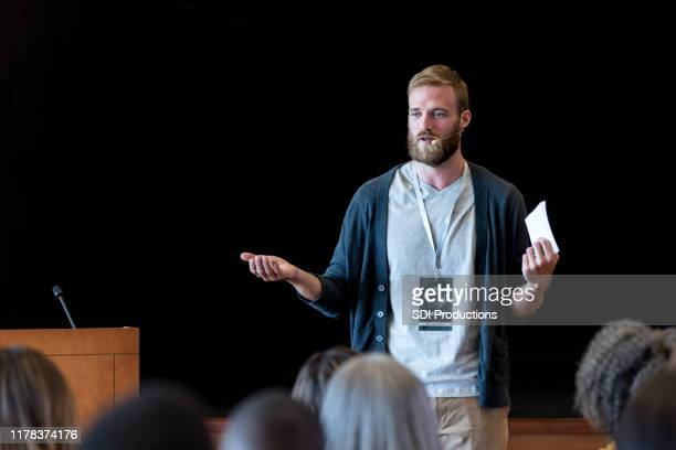 gesturing to make point, mid adult hipster speaks to audience - presentazione discorso foto e immagini stock
