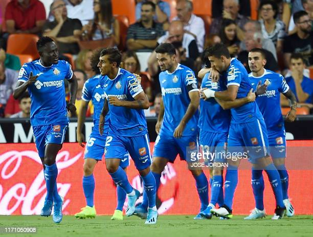 Getafe players celebrate the opening goal scored by Getafe's Spanish forward Jaime Mata during the Spanish league football match between Valencia CF...