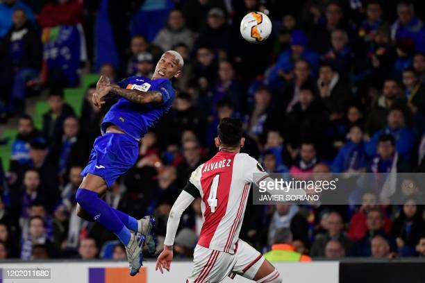 TOPSHOT Getafe´s Brazilian forward Deyverson jumps for the ball next to Ajax'Mexican midfielder Edson Alvarez during the Europa League round of 32...