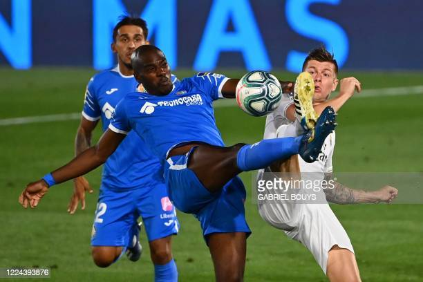 Getafe's Cameroonian defender Allan Nyom challenges Real Madrid's German midfielder Toni Kroos during the Spanish league football match Real Madrid...