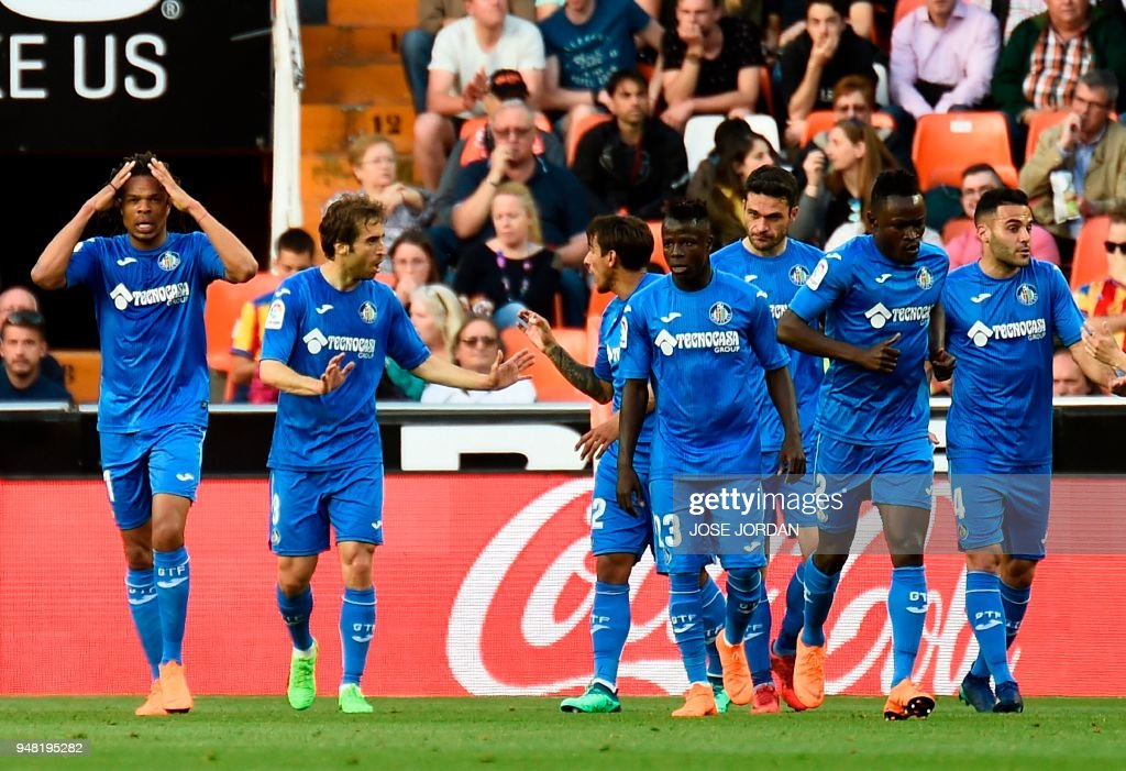 Getafe's French forward Loic Remy (L) celebrates with teammates after scoring during the Spanish league football match Valencia CF against Getafe CF at the Mestalla stadium in Valencia on April 18, 2018. /