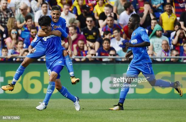 Getafe's midfielder from Japan Gaku Shibasaki celebrates a goal with teammates during the Spanish league football match Getafe CF vs FC Barcelona at...