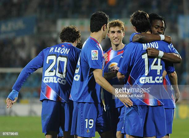 Getafe's players react after scoring a goal during a Spanish league football match Getafe/Mallorca at the Alfonso Perez Coliseum in Getafe, on March...