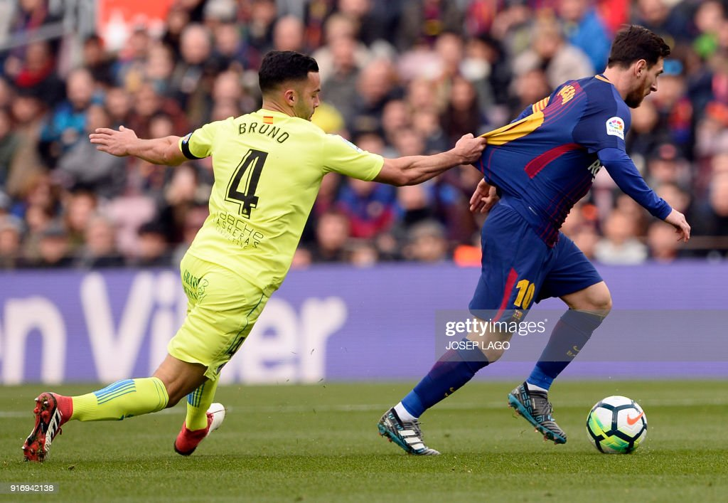 Getafe's Spanish defender Bruno Gonzalez (L) grabs the jersey of Barcelona's Argentinian forward Lionel Messi during the Spanish league football match between FC Barcelona and Getafe CF at the Camp Nou stadium in Barcelona on February 11, 2018. / AFP PHOTO / Josep LAGO