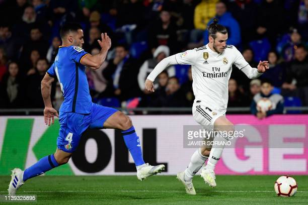 Getafe's Spanish defender Bruno Gonzalez vies with Real Madrid's Welsh forward Gareth Bale during the Spanish league football match between Getafe CF...