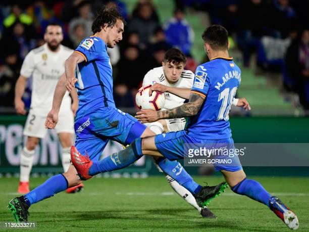 Getafe's Spanish defender Ignasi Miquel and Getafe's Uruguayan midfielder Mauro Arambarri try to block Real Madrid's Spanish midfielder Brahim Diaz'...