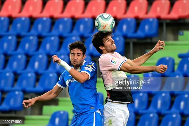 Getafe's Spanish forward Jaime Mata and Espanyol's French defender Sebastien Corchia jump for the ball during the Spanish league football match...