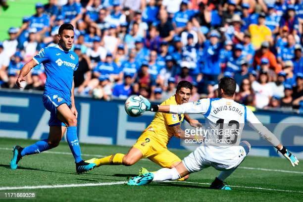 Getafe's Spanish goalkeeper David Soria stops the ball in front of Barcelona's Uruguayan forward Luis Suarez and Getafe's Spanish defender Bruno...
