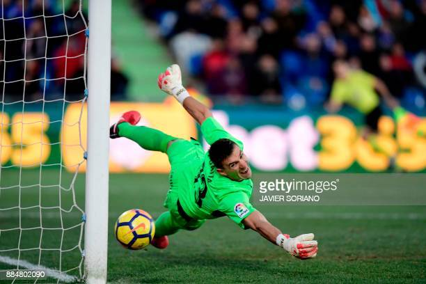 Getafe's Spanish goalkeeper Vicente Guaita dives to stop the ball during the Spanish league football match Getafe CF vs Valencia CF at the Col...