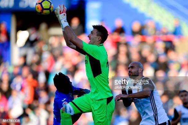 Getafe's Spanish goalkeeper Vicente Guaita jumps to grab the ball next to Getafe's Togolese defender Dakonam Djene and Valencia's Italian forward...