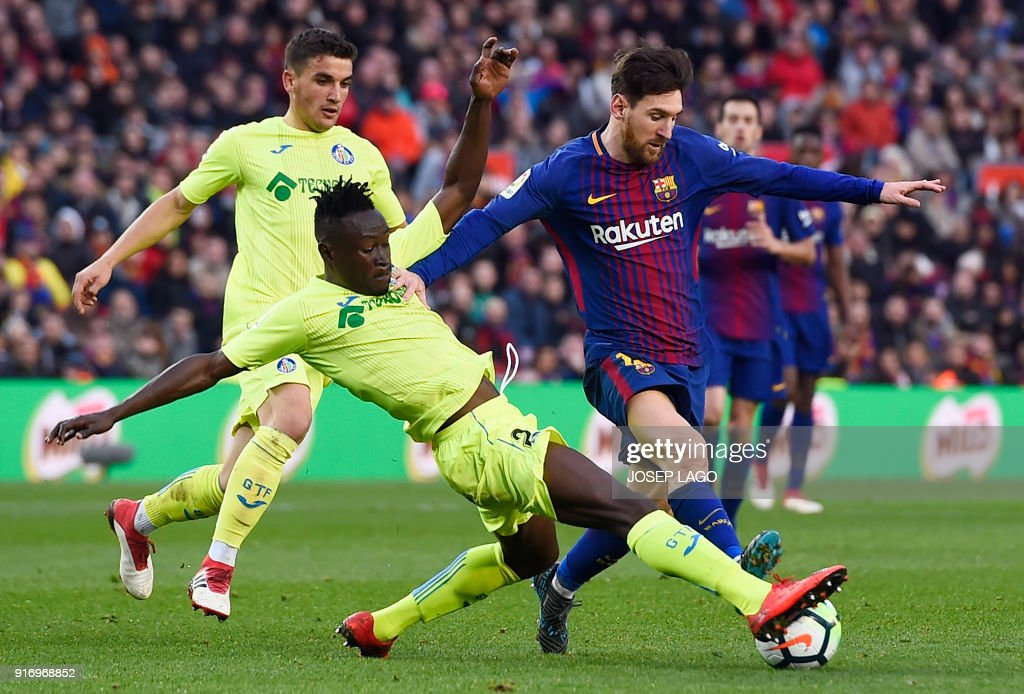 Getafe's Togolese defender Dakonam Djene (2L) vies with Barcelona's Argentinian forward Lionel Messi during the Spanish league football match between FC Barcelona and Getafe CF at the Camp Nou stadium in Barcelona on February 11, 2018. / AFP PHOTO / Josep LAGO
