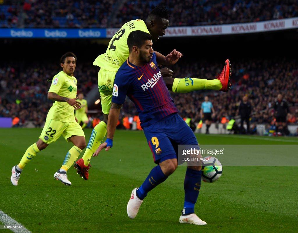 Getafe's Togolese defender Dakonam Djene (C) vies with Barcelona's Uruguayan forward Luis Suarez (R) during the Spanish league football match between FC Barcelona and Getafe CF at the Camp Nou stadium in Barcelona on February 11, 2018. / AFP PHOTO / Josep LAGO