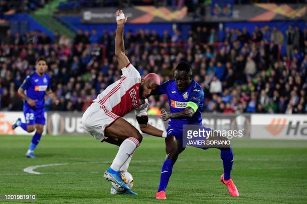 Getafe's Togolese defender Djene challenges Ajax´s Dutch forward Ryan Babel during the Europa League round of 32 football match between Getafe CF and...