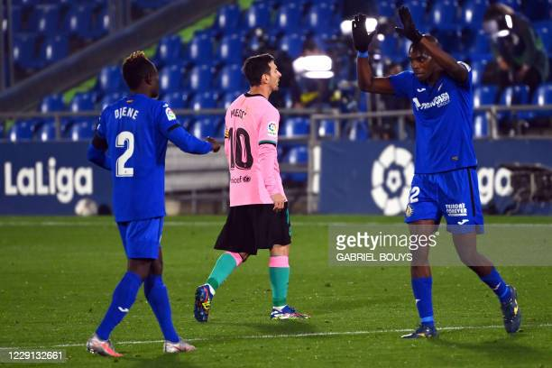 Getafe's Togolese defender Djene Dakonam and Getafe's Cameroonian defender Allan Nyom celebrate their victory as Barcelona's Argentine forward Lionel...