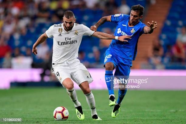 Getafe's Uruguayan defender Damian Suarez challenges Real Madrid's French forward Karim Benzema during the Spanish League football match between Real...