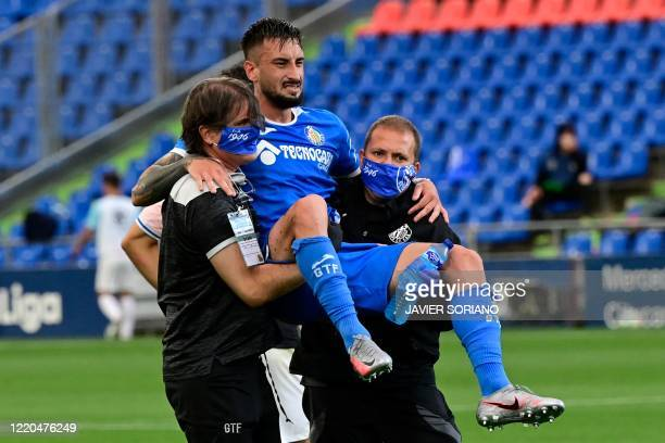 Getafe's Uruguayan defender Erick Cabaco is carried out of the pitch after suffering an injury during the Spanish league football match Getafe CF...