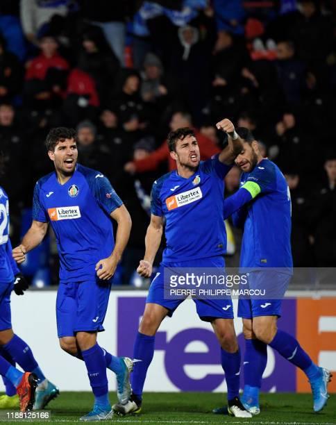Getafe's Uruguayan defender Leandro Cabrera celebrates scoring the opening goal with Getafe's Spanish forward Jaime Mata and Getafe's Spanish forward...