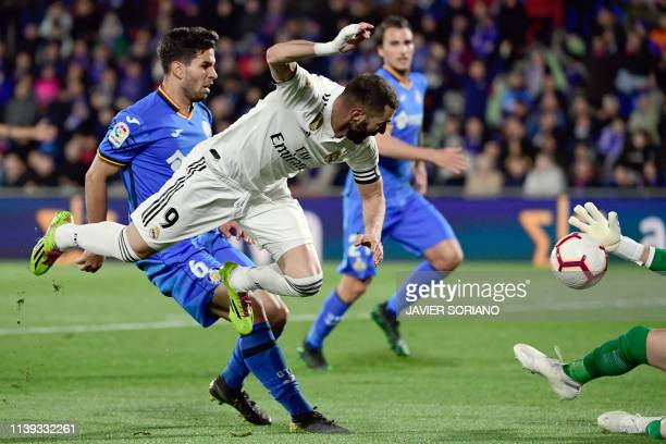 Getafe's Uruguayan defender Leandro Cabrera vies with Real Madrid's French forward Karim Benzema during the Spanish league football match between...