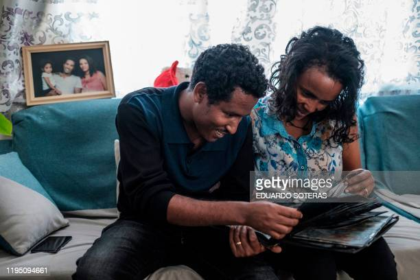 Getahun Fetana and his wife Emebet Melaku looks at photographs in a family album in their home in the city of Gondar Ethiopia on January 18 2020 He...