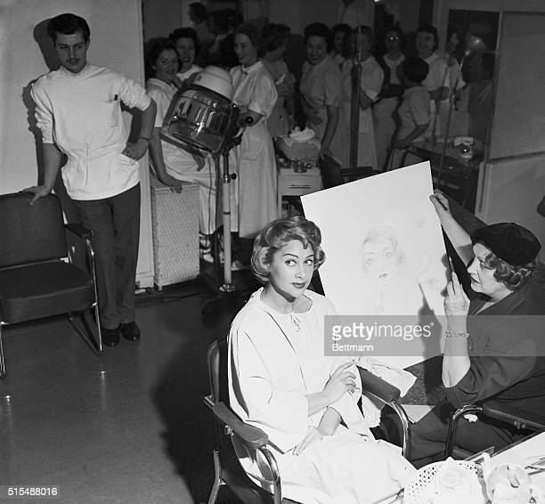 Getting a beauty treatment in pencil and in person at the same time lovely French actress Martine Carol poses for an artist in a Paris beauty shop In...
