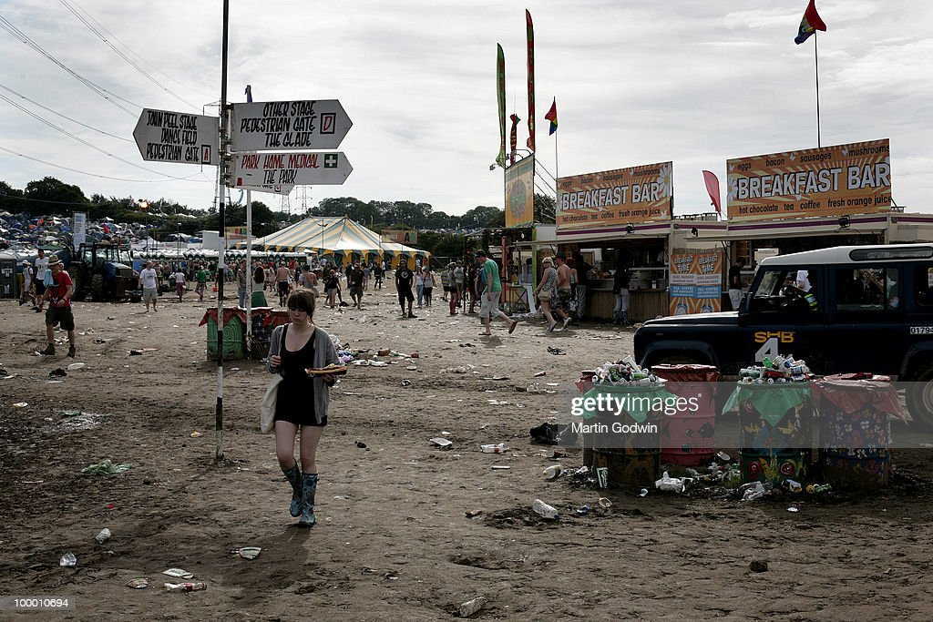 Getting breakfast on Sunday Morning amid the rubbish of the night before, and over flowing bins, with signpost and toilets in the background at Glastonbury, 28th June 2009.