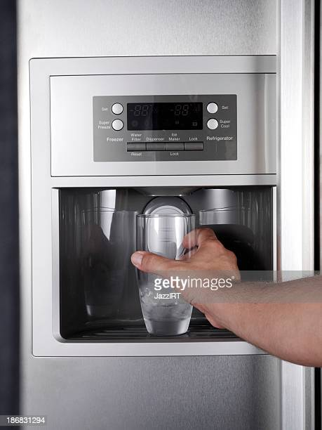 Getting glass of filtered water from refrigerator.