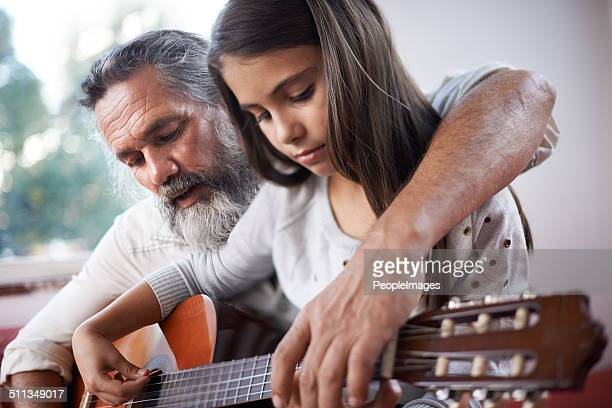 Getting her guitar lesson from her granddad