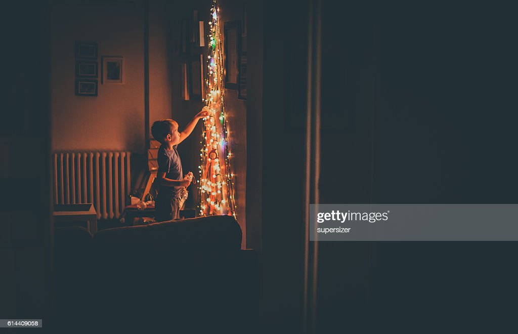 Young boy is getting ready for Christmas. The main focus are Christmas lights. The photo taken from the mirror