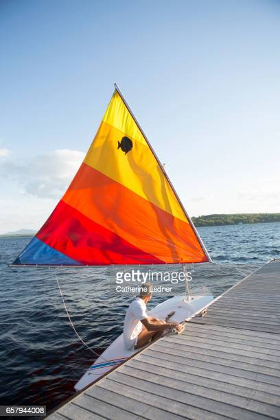 getting ready to sail the sunfish on the lake - sunfish stock photos and pictures