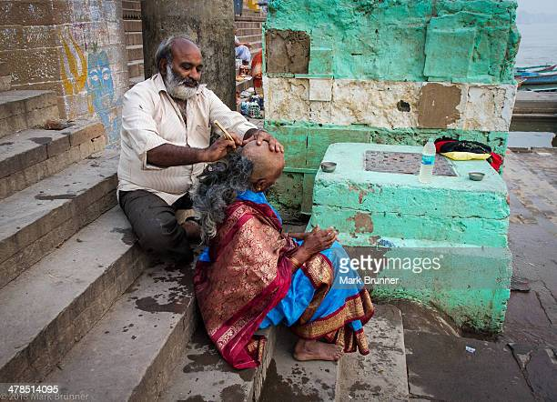 Getting the head shaved before bathing in the Ganges. The shaving of the head is done just prior to bathing in the river, so to be pure/clean.